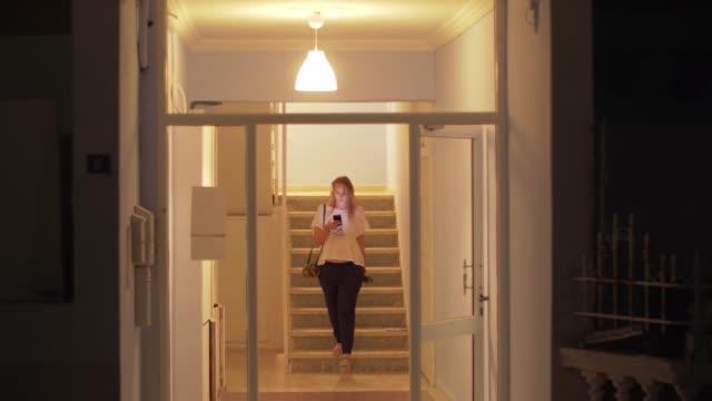 vídeos y material grabado en eventos de stock de mujer con móvil saliendo de casa por la noche - despedida