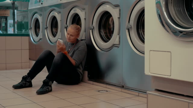 Woman with mobile waiting for the laundry video