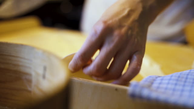 Woman with painted nails makes traditional handmade dumplings at home. Pierogi stuffed with meat, mushroom or potato stuffing. Lying dough on pastry board is sliced into similar pieces.