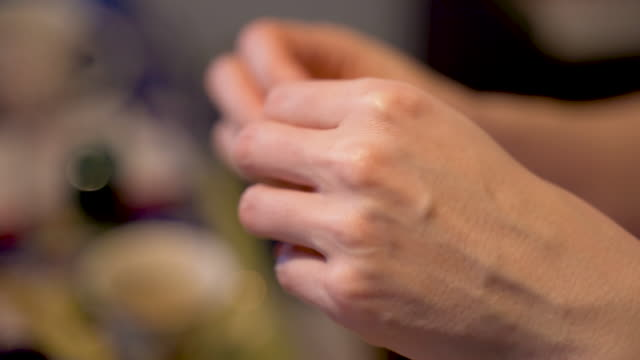 Woman with painted nails makes traditional handmade dumplings at home. Pierogi stuffed with meat, mushroom or potato stuffing. Each dumpling must be carefully glued.