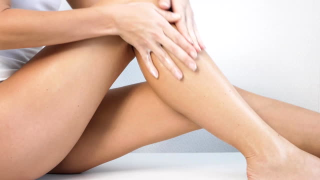Woman with perfect body applying refreshing cream or body lotion on her legs, Concept depilation, skincare, cosmetics video
