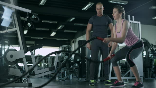 Woman with personal trainer working out with battle ropes video