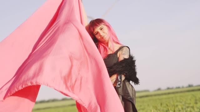 stockvideo's en b-roll-footage met vrouw met stukjes rode doek dansen in de buurt van het veld met wind generatoren. windmolen op zonsondergang. slow motion. stijlvolle hipster woman - roze haar