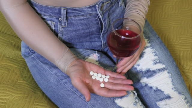 Woman with pills and glass of wine - vídeo