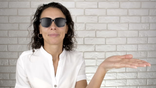 Woman with pinhole glasses. Woman with pinhole glasses. Shows hand. Eye care. eye chart stock videos & royalty-free footage