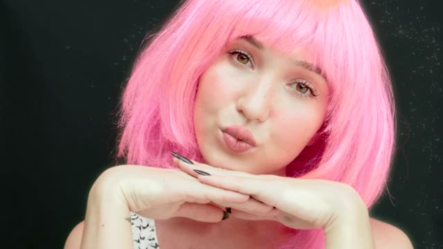 A woman with pink hair looks up and blinks quickly. Childish and naive look.