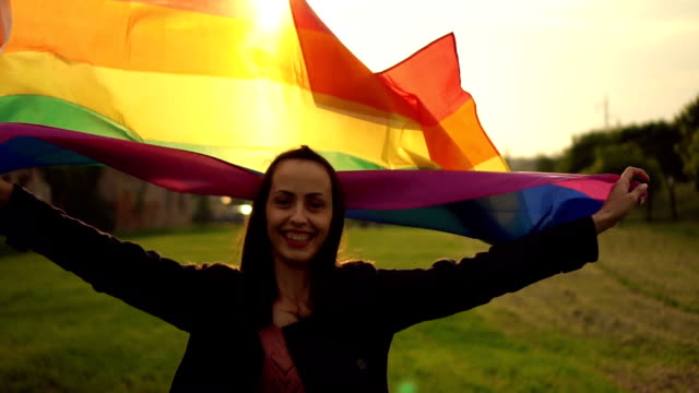 Woman with pride flag Lesbian woman running with a pride flag waving in the wind. transgender stock videos & royalty-free footage