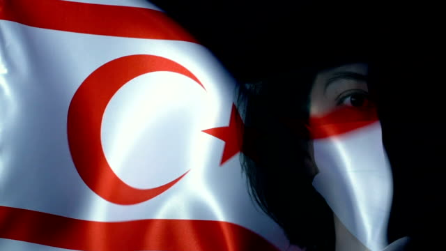 woman with protective face mask on cyprus turkish republic flag. protection for viruses and infections. - capelli neri video stock e b–roll