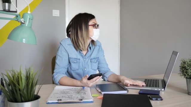 frau mit schützender gesichtsmaske arbeitet von zu hause aus - smartphone mit corona app stock-videos und b-roll-filmmaterial