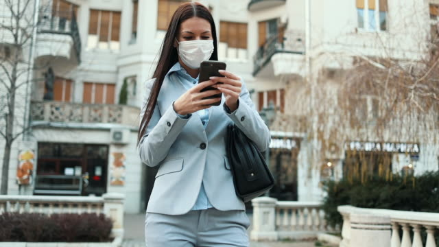 Woman with protective mask on city street Young and elegant business woman walking on empty city street and wearing protective mask to protect herself from dangerous flu or virus. Corona virus or Covid-19 concept. face mask videos stock videos & royalty-free footage