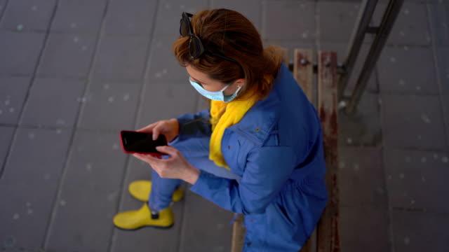 frau mit schutzmaske sms an einem busbahnhof - smartphone mit corona app stock-videos und b-roll-filmmaterial