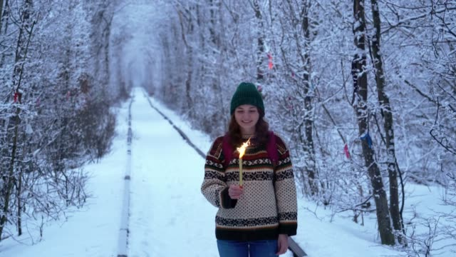 Woman with  pyrotechnics standing in Tunnel of Love in winter