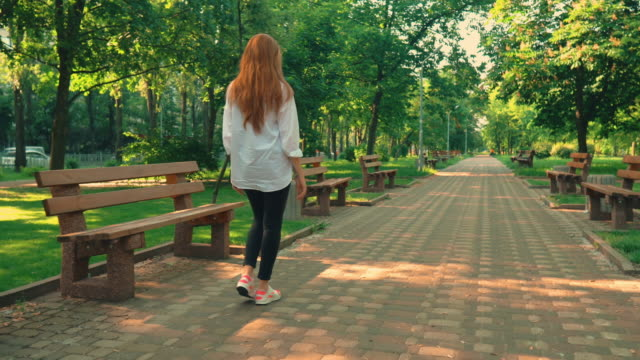 woman with red hair turn to the camera stroll in spring town follow me concept redhead girl walking on the street surrounded green trees casual female walks outdoors dyed red hair stock videos & royalty-free footage