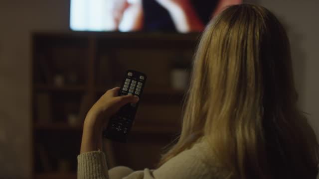 uzaktan kumandalı kadın tv kanallarını değiştiriyor - sarı saç stok videoları ve detay görüntü çekimi
