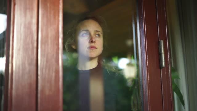 kvinna med sorgligt ansikte tittar ut genom fönstret inifrån hemmet - fånga bildbanksvideor och videomaterial från bakom kulisserna