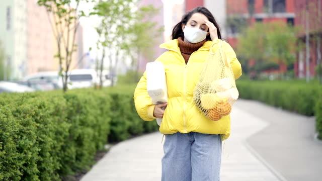 kvinna med safity mask och shopping saker går på gatan. - face mask bildbanksvideor och videomaterial från bakom kulisserna