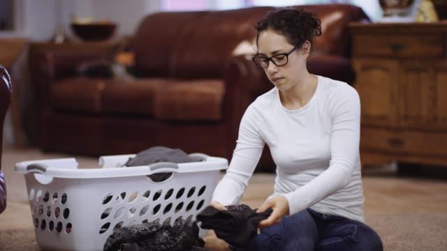 Frau mit schweren Schmerzen im Beckenbereich beim Falten der Wäsche – Video