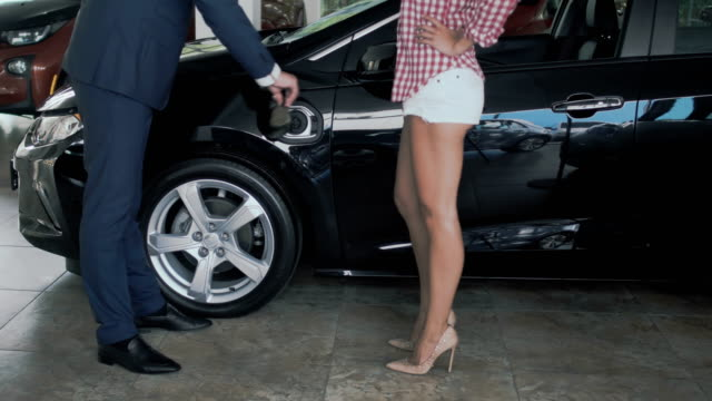 Woman with sexy legs and salesman are charging electric car in car dealership video