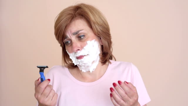 woman with shaving foam on her face holding a razor - baffo parte del corpo animale video stock e b–roll
