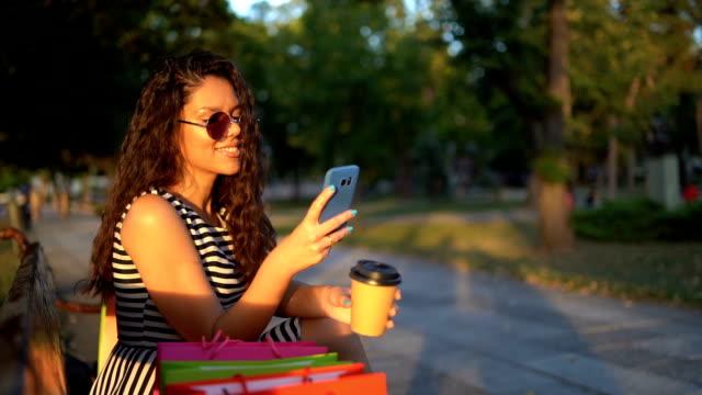 ショッピングバッグを持つ女性 - ベンチ点の映像素材/bロール