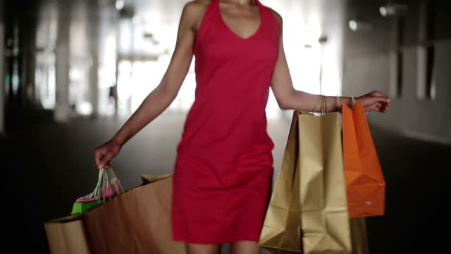 Woman with shopping bags walking in a mall video
