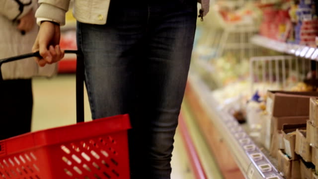 woman with shopping basket choosing refrigerated groceries at the supermarket. - cestino video stock e b–roll