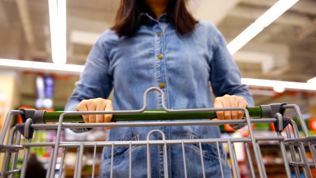 Woman with shopping Cart in supermarket Woman with shopping Cart in supermarket consumerism stock videos & royalty-free footage