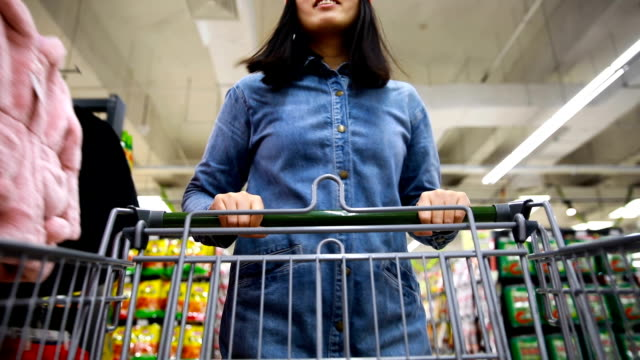 Woman with shopping Cart in supermarket Woman with shopping Cart in supermarket shopping cart stock videos & royalty-free footage