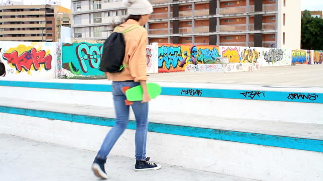 Woman with skateboard walking and sitting in a skatepark