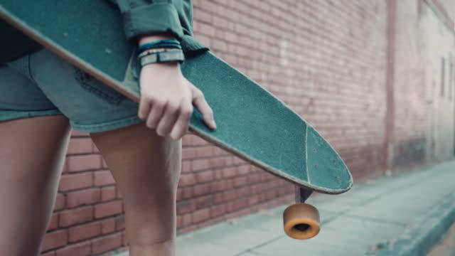 Mujer caminando por la calle con monopatín - vídeo