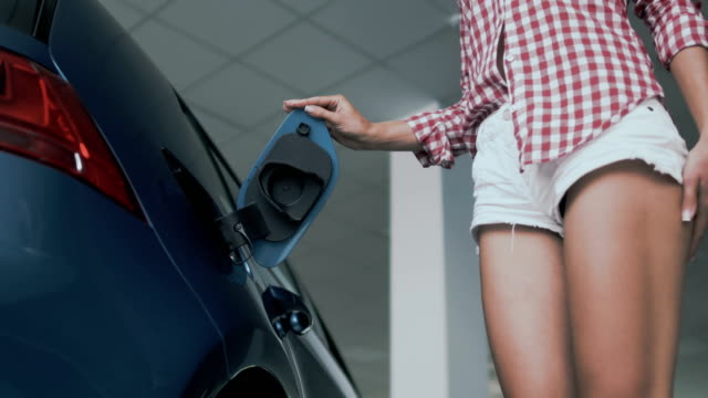 Woman with slim tanned legs puts the charging in power socket in electric car video