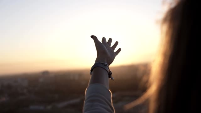Woman with smart watches touching the sunlight by hand over beautiful sky background while standing on the roof. Happy woman looking at sunrising through his fingers and waving her hand. Slow motion