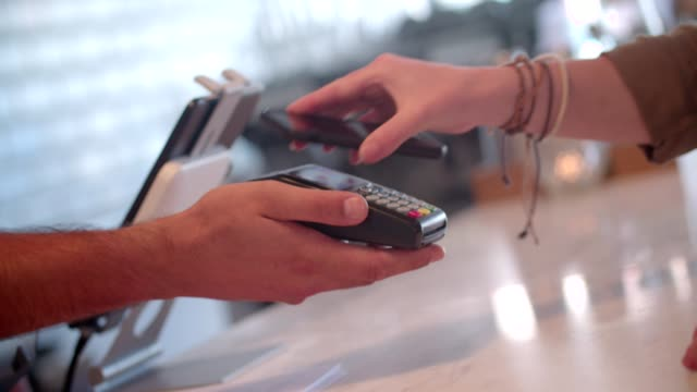 woman with smartphone paying at restaurant using contactless technology - contactless payment stock videos & royalty-free footage