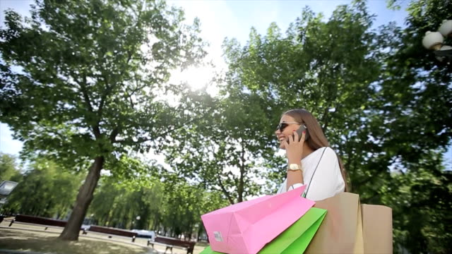 Woman with smartphones and shopping bags walking in a city video