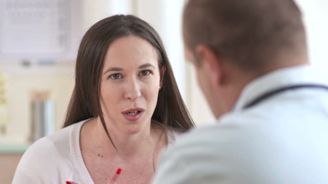 HD: Woman With  Sore Throat Problems HD1080p: PANNING shot of a mid-adult woman explaining about sore throat problems to her doctor at diagnostic center. mid adult stock videos & royalty-free footage