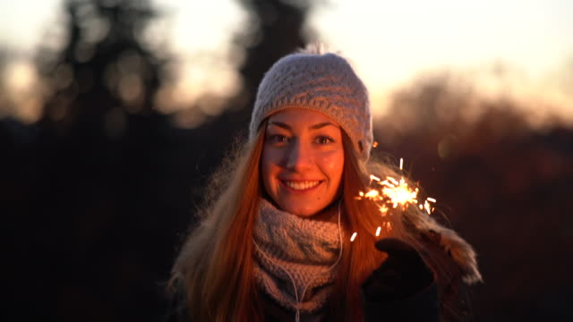 woman with sparklers smiling to the camera - ventenne video stock e b–roll