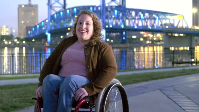 woman with spina bifida in wheelchair on city waterfront - body positive video stock e b–roll