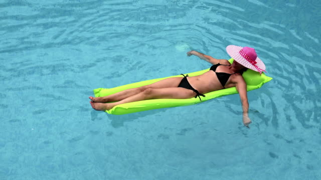 Woman with straw hat relaxing on inflatable mattress at pool video
