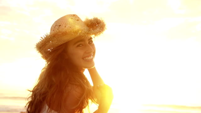 Woman with straw hat smiling and laughing at camera video