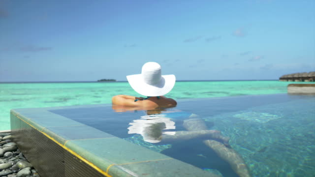 donna con cappello di sole in piscina sull'oceano rilassante in maldive - località turistica video stock e b–roll