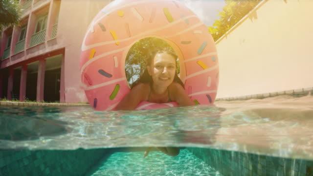 kvinna med sol glasögon i blå bikini ligger i uppblåsbar rosa donut flyta i poolen på soliga sommar dag. titta på kameran. kvinna bikini pool på vattenmelon gummi ring avkopplande semester - inflatable ring bildbanksvideor och videomaterial från bakom kulisserna