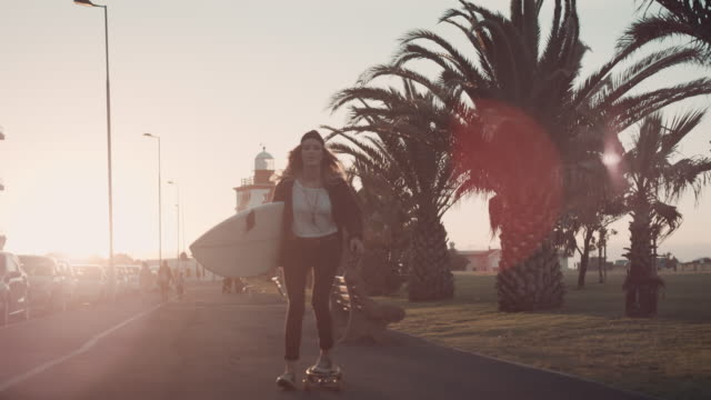 Woman with surfboard skating at beach video