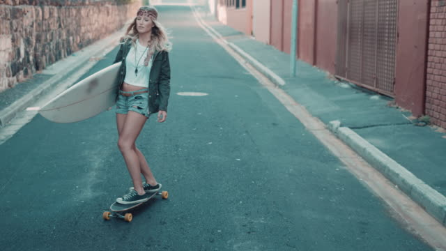 Woman with surfboard skating on street video