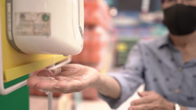 vídeos y material grabado en eventos de stock de mujer con mascarilla quirúrgica usando dispensador automático de desinfectante de manos para la prevención de infecciones - hand sanitizer