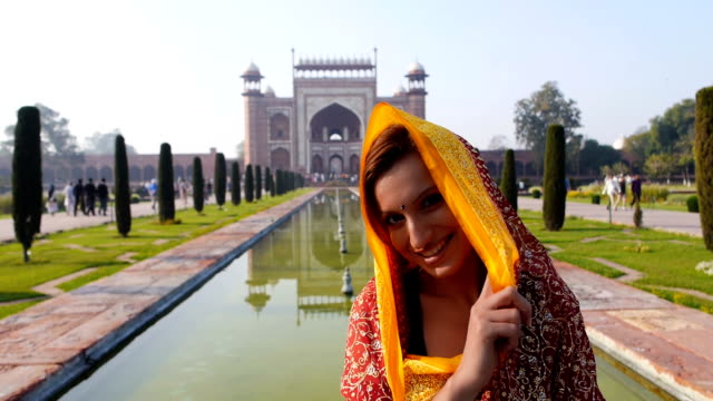 Woman with Taj Mahal entrance at the back Woman with Taj Mahal entrance at the back sari stock videos & royalty-free footage