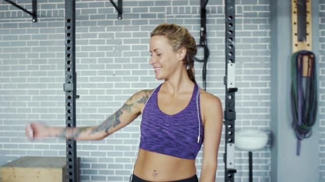 woman with tattoos flexing muscles and smiling at camera in gym - napinać mięśnie filmów i materiałów b-roll
