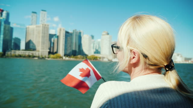 A woman with the canada flag looks at Toronto cityscape from the ship. Tourism in Canada concept video