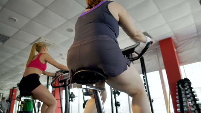 Woman with thick legs pedalling on stationary bike in the gym, weight loss video