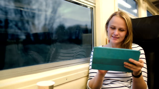 Woman with touchpad and tea in train video