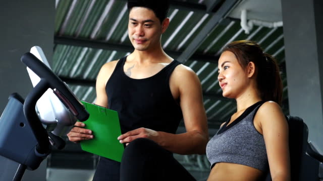woman with trainer working out on exercise in gym video